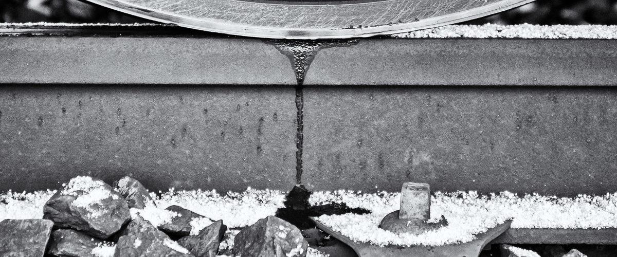 """Planche 20 : """"La roue qui saigne"""". Détail de la zone de contact rail-roue un jour de neige. Janvier 2010. [Silver Efex]"""