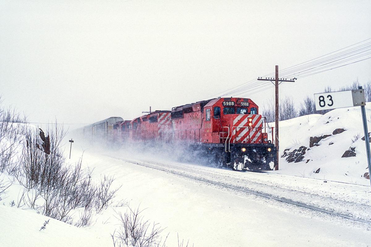 Un train de voitures ou camionettes est photoraphié derrière un trio de SD40-2 du Canadien Pacifique.