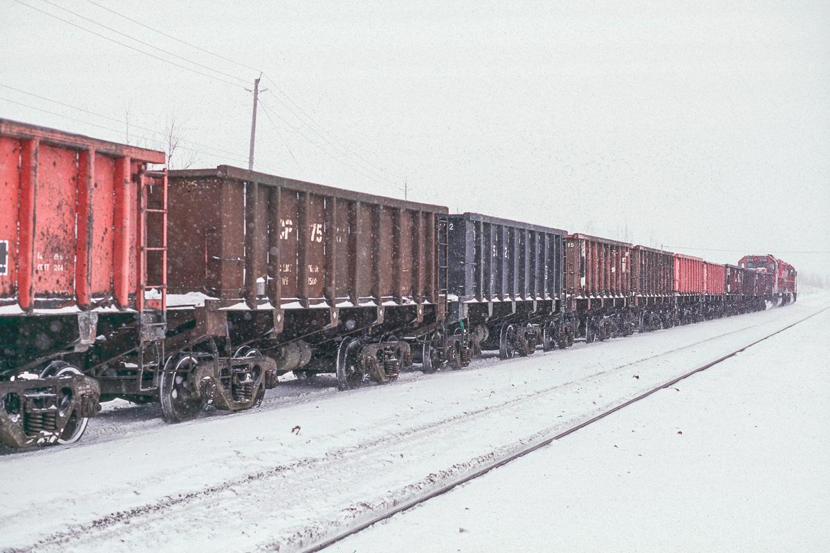 Un convoi attend le passage d'un train de container pour continuer son voyage vers une des nombreuses mines de nickel de la région de Sudbury.