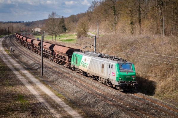 La BB27161 tire un court train de wagons-trémies vides à destination des carrières de Raon-l'Etape. Cette locomotive porte aujourd'hui une livrée Akiem grise. Avril 2007.