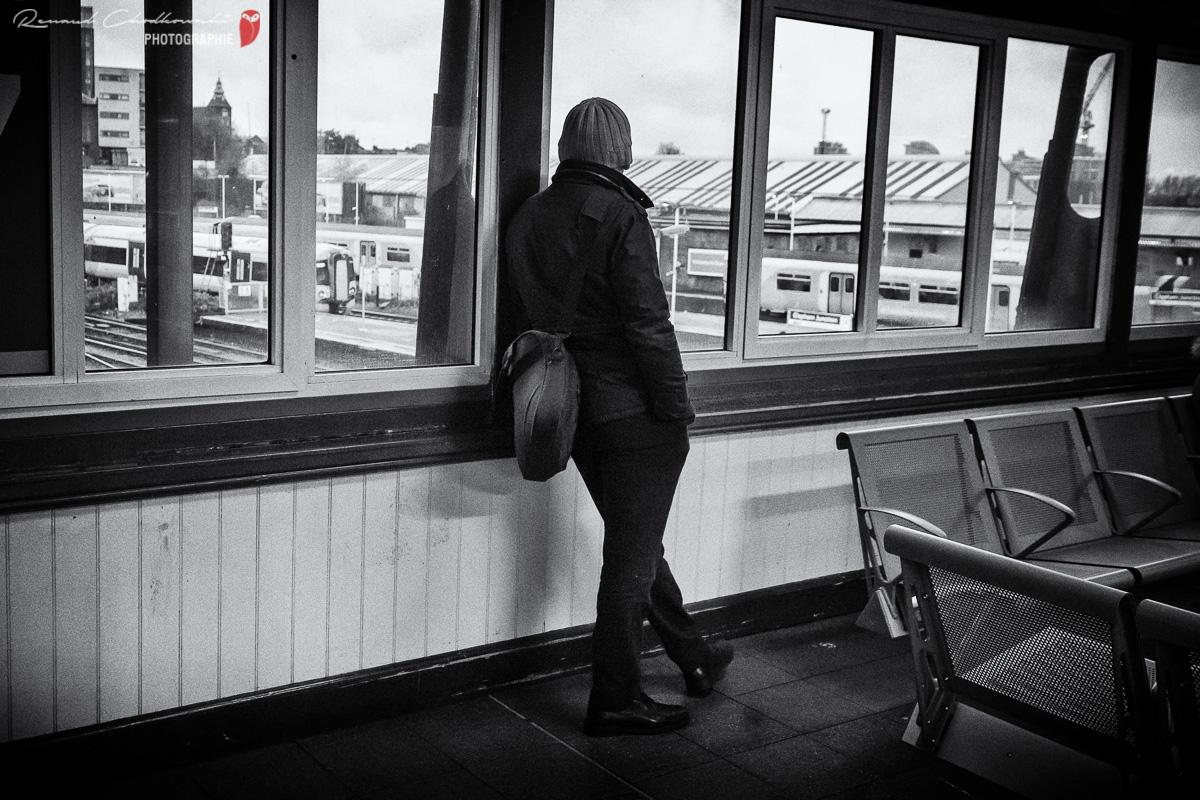 Un homme observe les trains depuis la passerelle principale de la gare de Clapham Junction.
