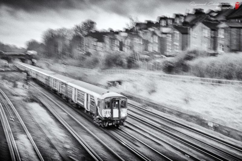 Flou filé partiel d'un train de banlieue se dirigeant vers le sud de Londres.