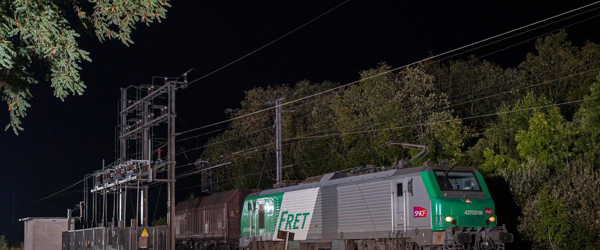 La BB27020 et son train de fret diffus passe au droit d'un installation électrique.